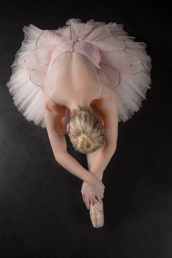 Behagfull ballerina som böjer framåtriktat i rosa ballerinakjol arkivbild