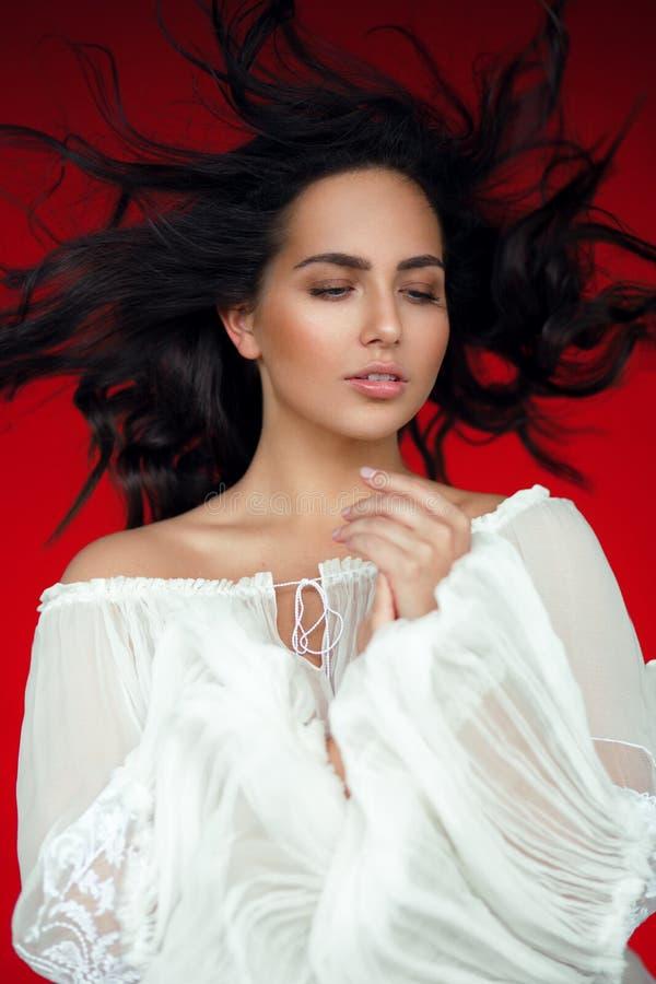 Behagfull brunettkvinna som ner ser, isoalted på en röd bakgrund som är rak flyga hans hår, royaltyfri fotografi