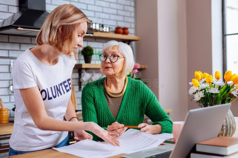 Behagfull dam som har konversation med den pensionerade kvinnan om låndokument arkivfoto