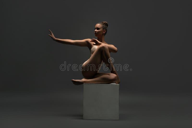 Behagfull flicka i kroppsammanträde på ett kubskott arkivfoto