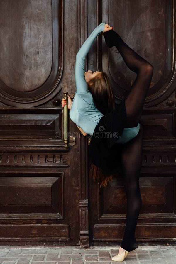 Behagfull härlig flickaballerina som poserar på gatan av dörren för tappningteaterträ arkivbild