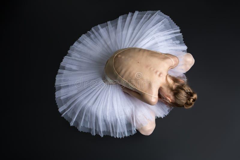 Behagfullt ballerinasammanträde på golvet royaltyfri fotografi