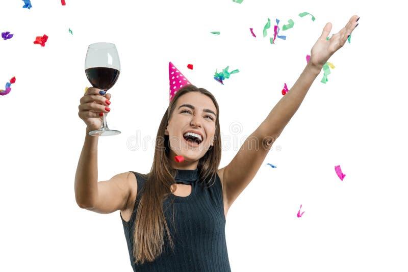 Behagfullt och att le den unga brunettflickan i partihatt med exponeringsglas av rött vindans under konfettier och skratta som är royaltyfria foton