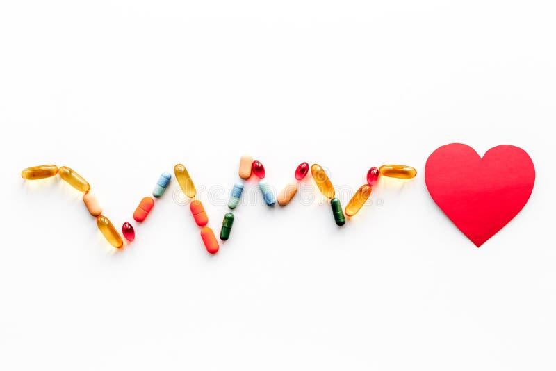 Behandel hart Document hart en pillen in vorm van cardiogram op witte hoogste mening als achtergrond copyspace stock foto