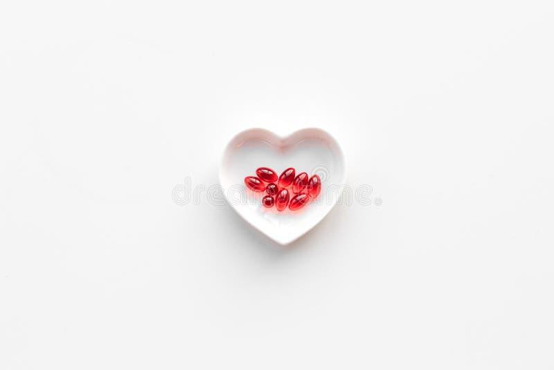 Behandel hart Pillen in kom in vorm van hart op witte hoogste mening als achtergrond copyspace stock fotografie