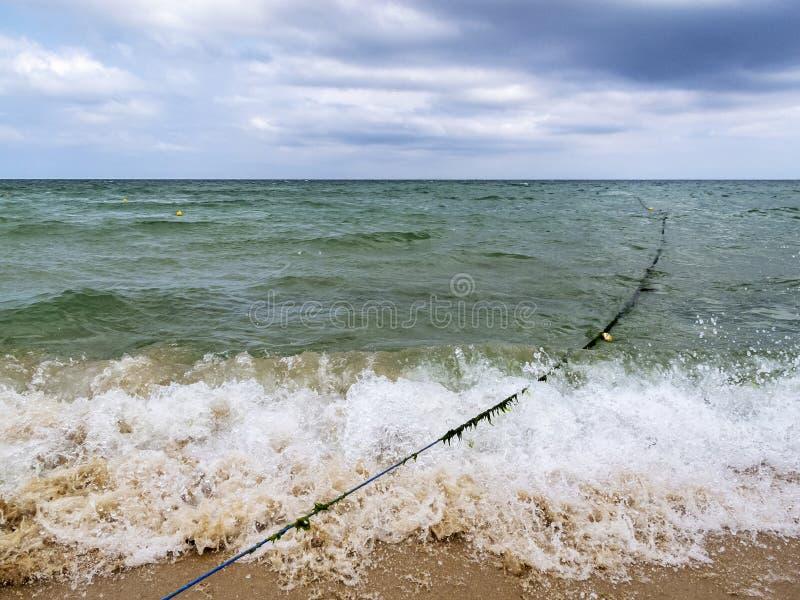 Behandeld met de kabel van de zeewierboei door een brekende golf op een zandig strand van de Zwarte Zee, Primorsko, Bulgarije royalty-vrije stock afbeelding