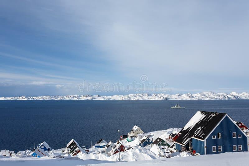 Behandeld in sneeuw inuit huizen bij de fjord met afdrijvend schip, Nu stock foto's