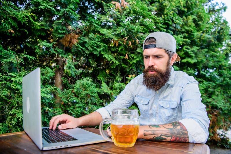 Behandelende klantenmededeling Zakenman die bedrijfsmededeling heeft door laptop Hipster die van bierbar werken met stock fotografie