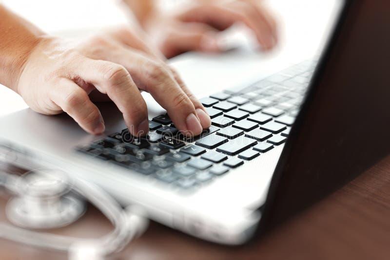 Behandeln Sie das Arbeiten mit Laptop-Computer im medizinischen Arbeitsplatz lizenzfreies stockfoto