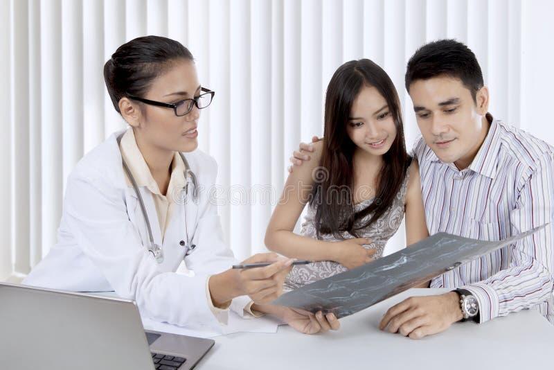 Behandeln Sie das Erklären eines Röntgenstrahlergebnisses ihrem Patienten stockfotografie