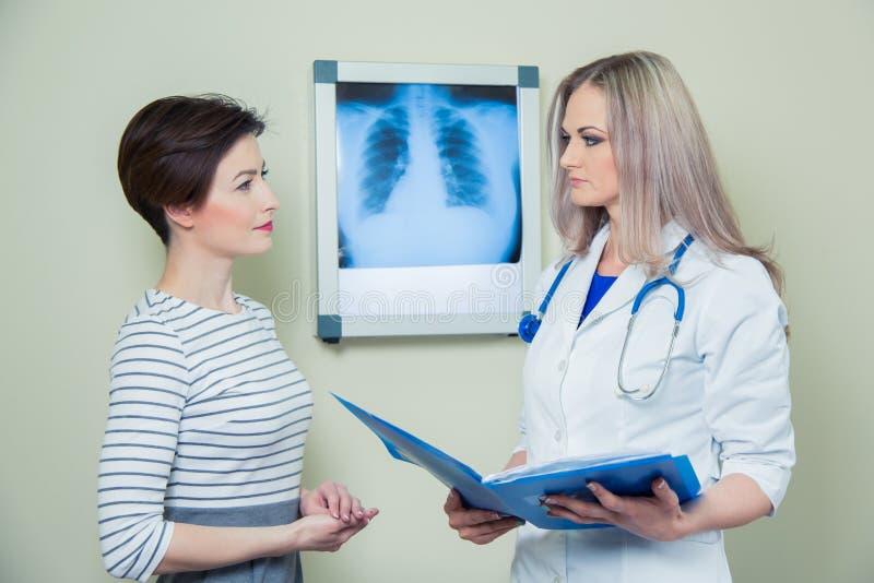 Behandeln Sie das Erklären von Diagnose ihrem weiblichen Patienten, der Röntgenaufnahme analysiert stockbild