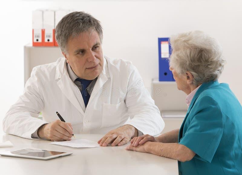 Behandeln Sie das Erklären von Diagnose seinem älteren weiblichen Patienten lizenzfreies stockfoto