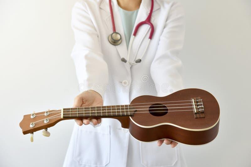 Behandeln Sie das Geben Ukulele des Musikinstrumentes, Musiktherapiekonzept stockbilder