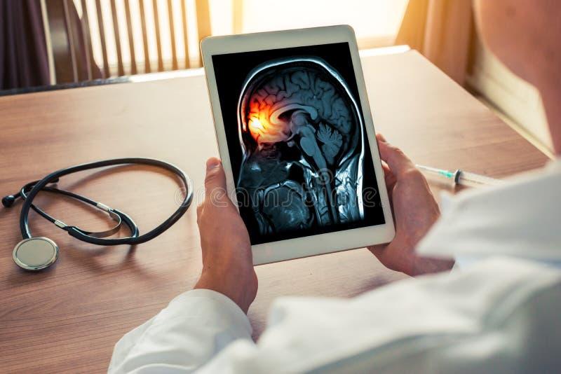 Behandeln Sie das Halten einer digitalen Tablette mit Röntgenstrahl des Gehirn- und Schädelskeletts Kopfschmerzen-, Meningitis- u lizenzfreie stockfotografie