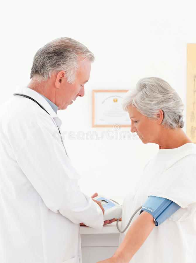 Behandeln Sie das Nehmen des Blutdruckes seines Patienten lizenzfreie stockbilder