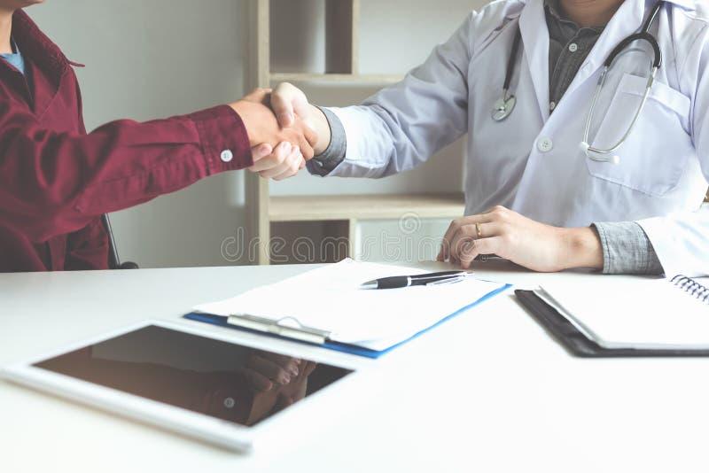 Behandeln Sie das Rütteln von Händen mit älterem Patienten im Büro stockbild
