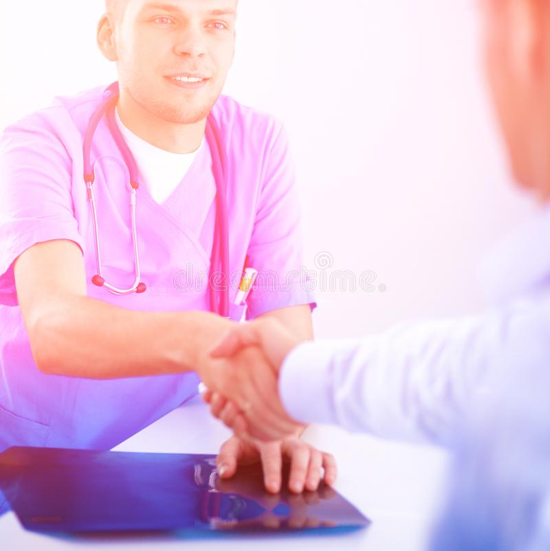 Behandeln Sie das Rütteln von Händen mit einem Patienten und auf dem Schreibtisch im Büro sitzen stockbilder