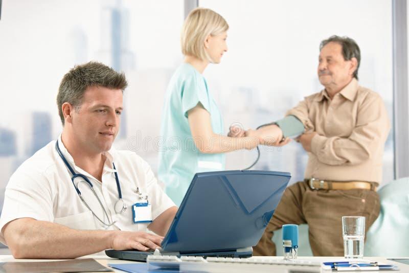 Behandeln Sie das Sitzen am Schreibtisch, überprüfenpatient der Krankenschwester. lizenzfreie stockfotografie