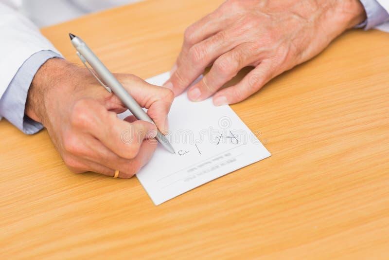 Behandeln Sie das Sitzen an seinem Schreibtischschreiben auf Verordnungsauflage stockfotografie