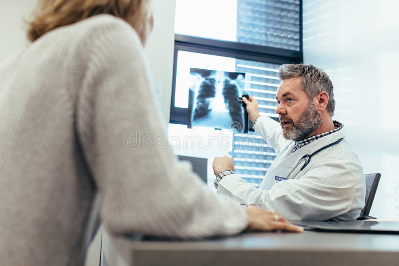 Behandeln Sie das Zeigen des Röntgenstrahls zu seinem Patienten im Ärztlichen Dienst stockbilder