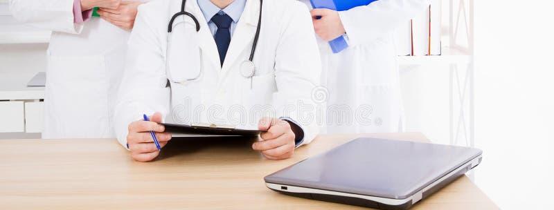 Behandeln Sie die Aufstellung im B?ro mit medizinischem Personal, er tr?gt ein Stethoskop stockbilder