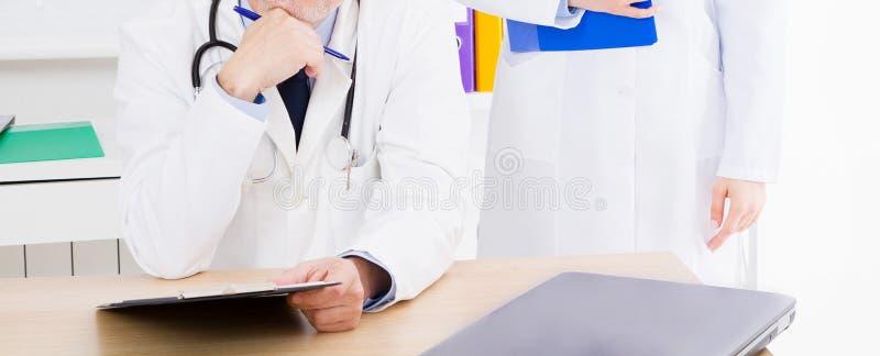 Behandeln Sie die Aufstellung im B?ro mit medizinischem Personal, er tr?gt ein Stethoskop lizenzfreies stockbild