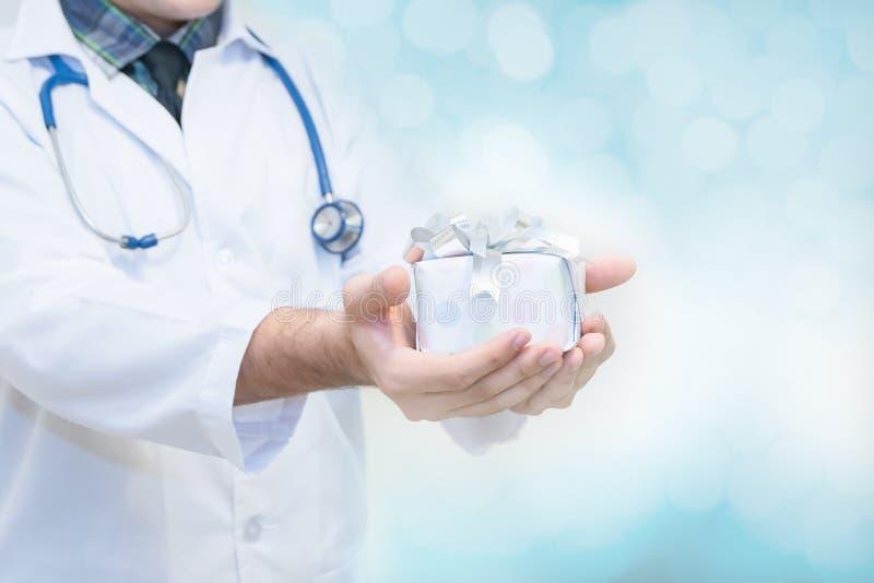 Behandeln Sie die Hände, die Geschenkbox mit Band, Geschenke für Patientenkonzept halten stockbild