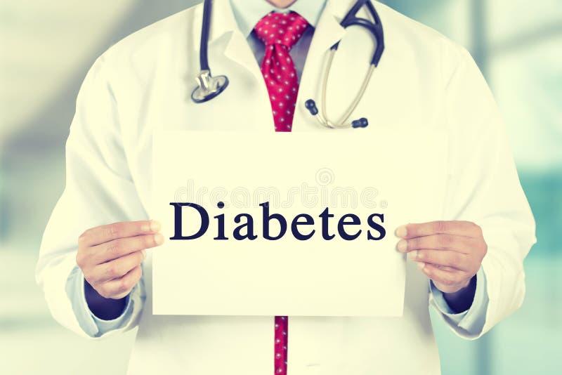 Behandeln Sie die Hände, die weißes Kartenzeichen mit Diabetestext halten stockbild