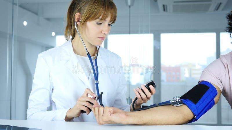 Behandeln Sie die Prüfung des Blutdruckes des Patienten in der Klinik stockfoto
