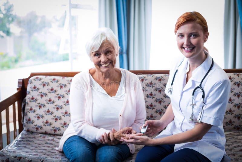 Behandeln Sie die Prüfung eines Patientenglukoseniveaus unter Verwendung eines digitalen glucometer lizenzfreie stockfotografie