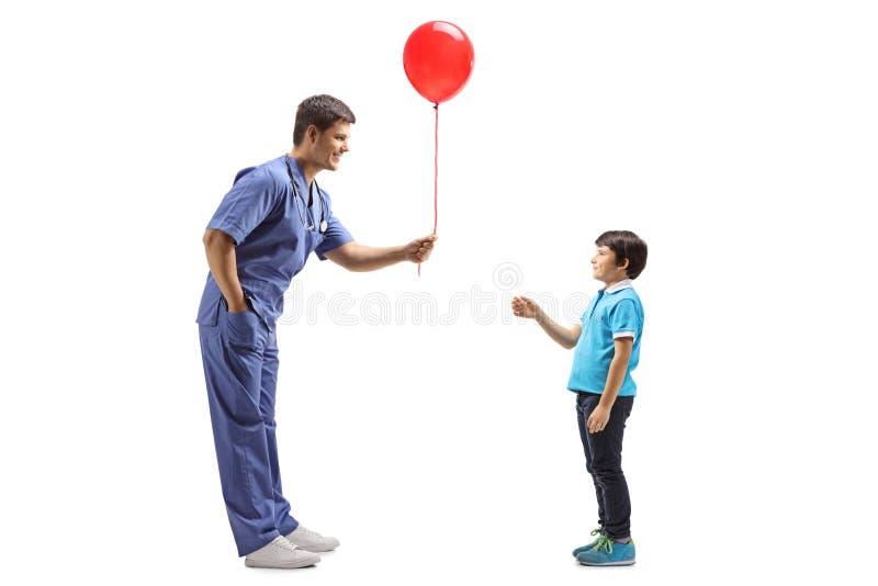 Behandeln Sie in einer blauen Uniform, die einem kleinen Jungen einen Ballon gibt lizenzfreie stockfotos