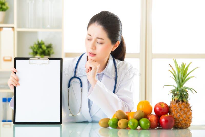 Behandeln Sie Ernährungswissenschaftler mit Früchten und dem Halten des leeren Klemmbrettes lizenzfreie stockbilder