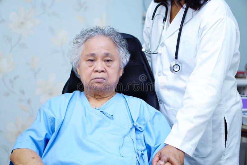 Behandeln Sie Hilfe und interessieren Sie sich den asiatischen älteren oder älteren Frauenpatienten alter Dame, der auf Rollstuhl stockfotografie