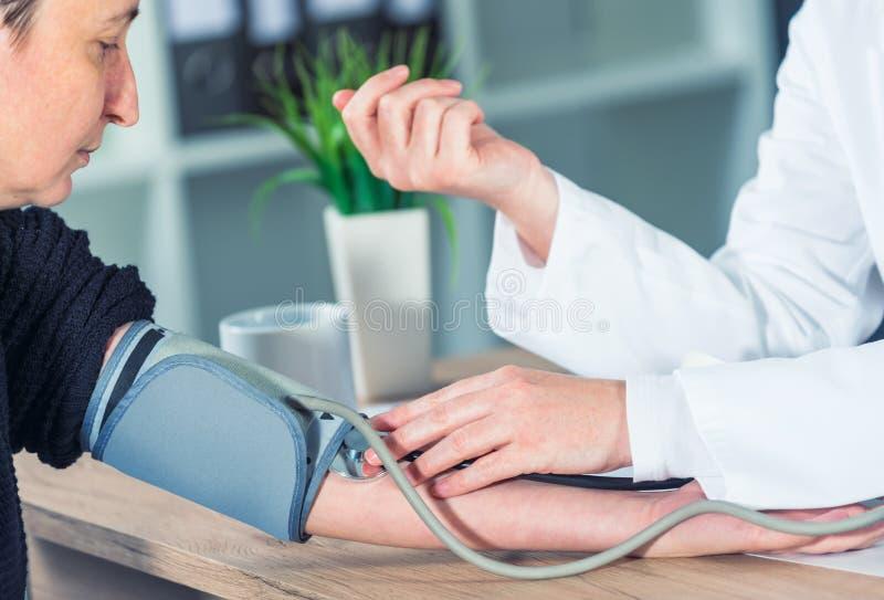 Behandeln Sie messenden Blutdruck des Kardiologen des weiblichen Patienten lizenzfreies stockbild