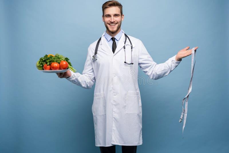 Behandeln Sie mit einem messenden Band und einer Platte mit dem Gemüse und Frucht, die auf hellblauem Hintergrund lokalisiert wer stockbild