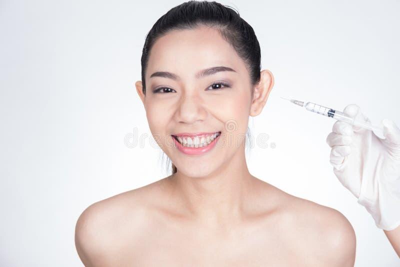 Behandeln Sie ` s Hand, die botox Einspritzung in Mädchen ` s Gesicht macht junges Asien lizenzfreies stockbild