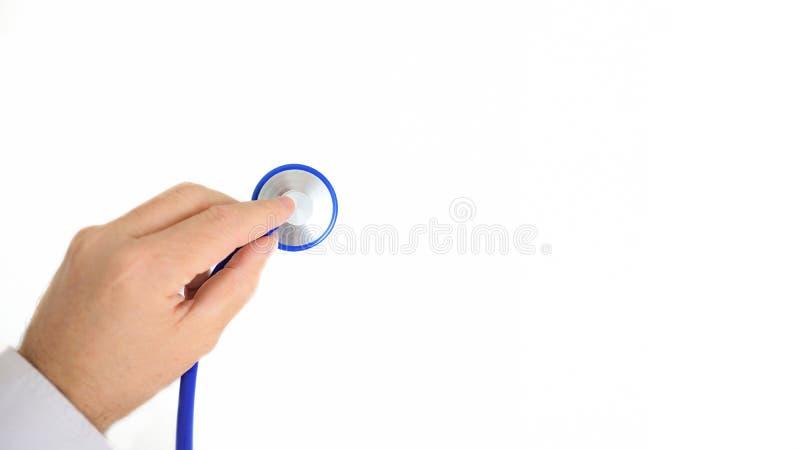 Behandeln Sie ` s Hand, die ein Stethoskop gegen einen weißen Hintergrund hält lizenzfreies stockbild