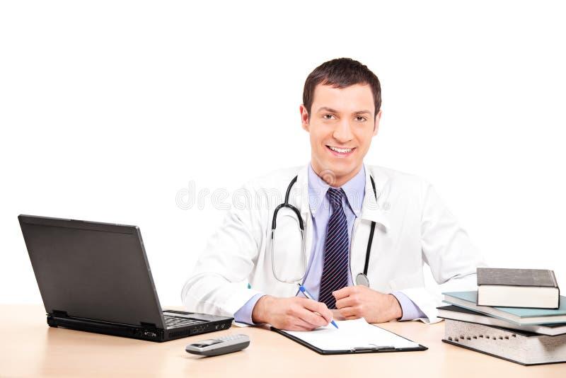 Behandeln Sie Schreiben auf einem Klemmbrett, das an seinem Schreibtisch setzt lizenzfreie stockfotos