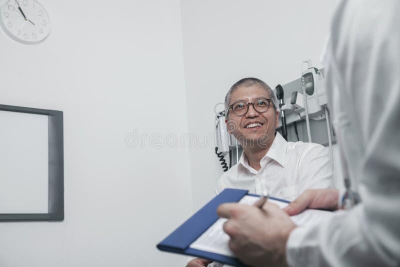 Behandeln Sie Schreiben auf medizinischem Diagramm mit einem lächelnden Patienten lizenzfreie stockbilder