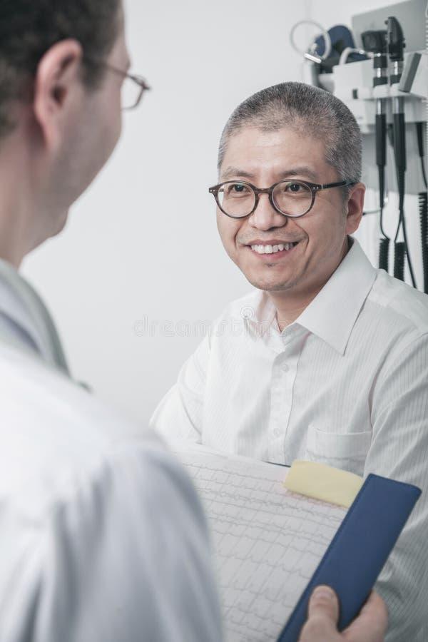 Behandeln Sie Schreiben auf medizinischem Diagramm mit einem lächelnden Patienten stockbilder