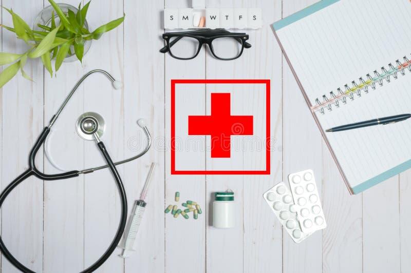 Behandeln Sie Tabelle mit medizinischen Einzelteilen, Stethoskop und Pillen stockbilder