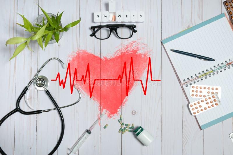 Behandeln Sie Tabelle mit medizinischen Einzelteilen, Stethoskop und Pillen stockbild