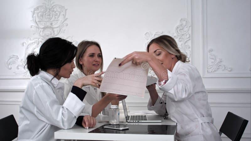 Behandeln Sie und zwei Studentinnen, die mit Kardiogramm im Büro arbeiten lizenzfreies stockbild