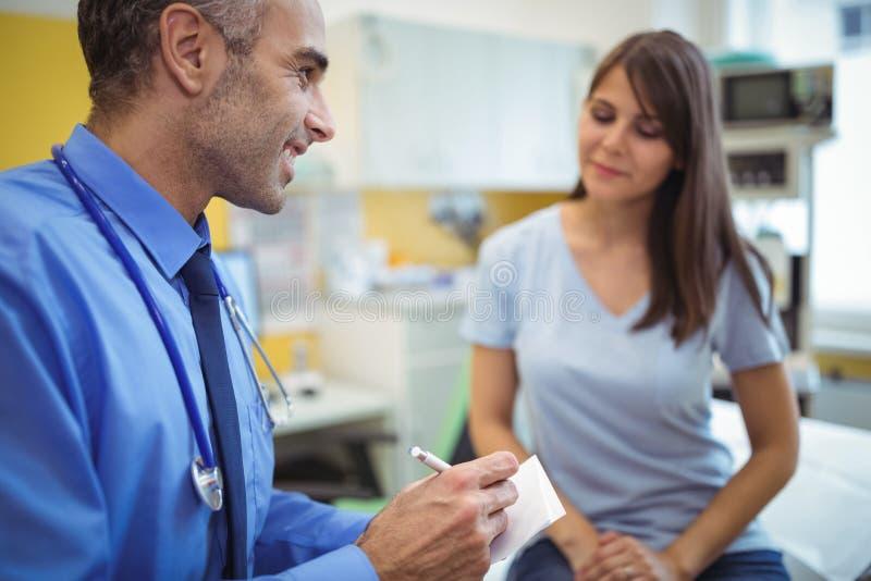 Behandeln Sie Wechselwirkungsschreiben auf Papier bei der Konsultierung des Patienten lizenzfreie stockbilder