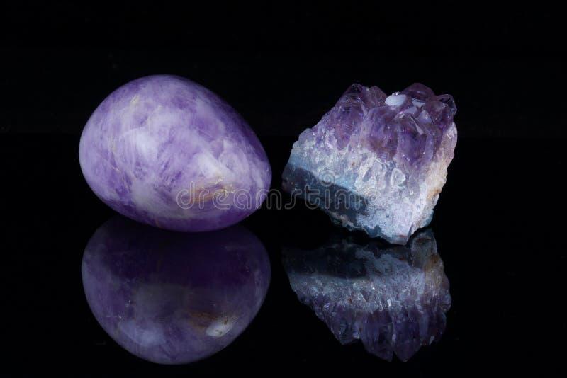 Behandelter Amethyst und Bergkristall auf einem dunklen Hintergrund mit Reflexion stockfotografie