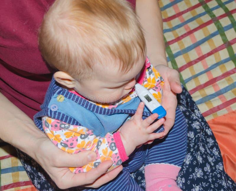 Behandla som ett barn är sjuk med en termometer på musen på mina händer för mamma` s royaltyfria foton