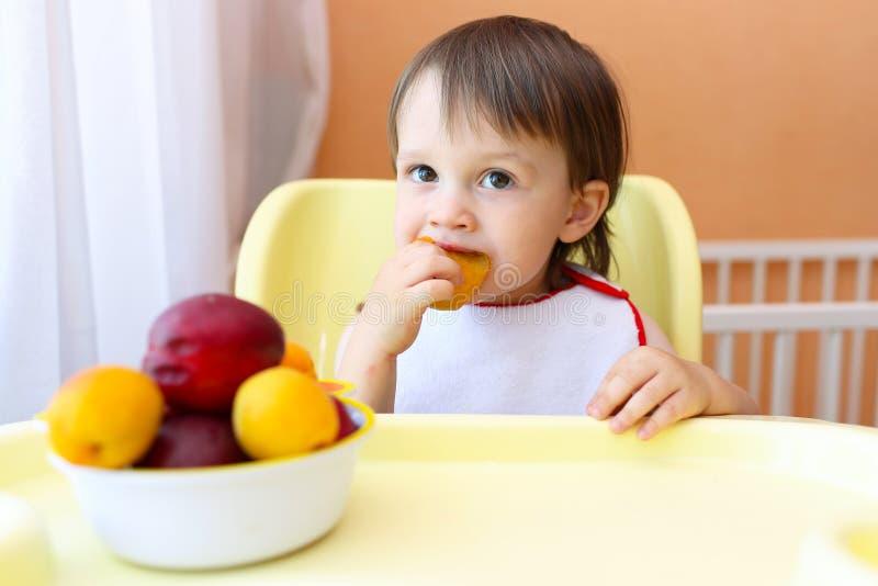 behandla som ett barn äta frukter royaltyfri foto