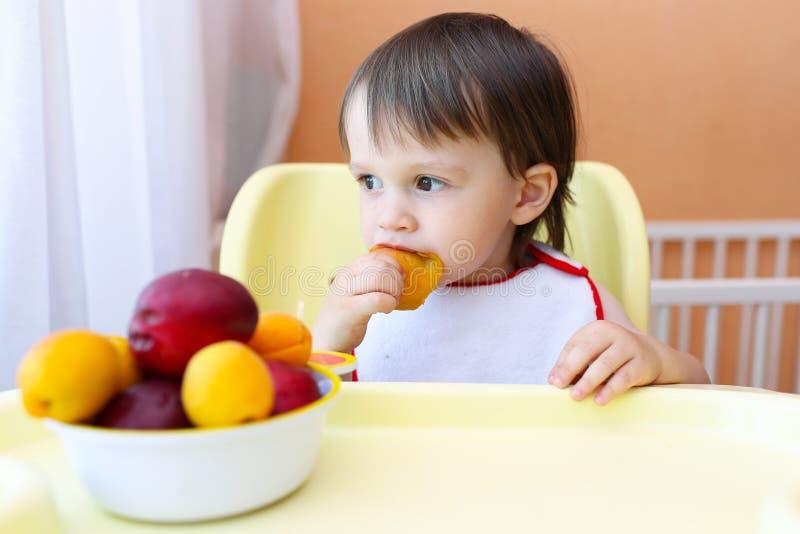 Behandla som ett barn äta frukter hemma royaltyfri foto