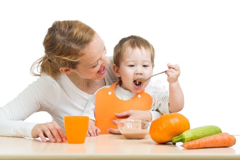 Behandla som ett barn äta grönsaker av den själva skeden och modern arkivbild