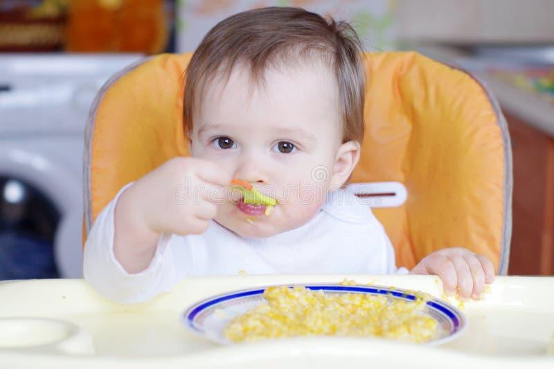 Behandla som ett barn åldern av 1 år äter ris-mjölkar med pumpa royaltyfri fotografi